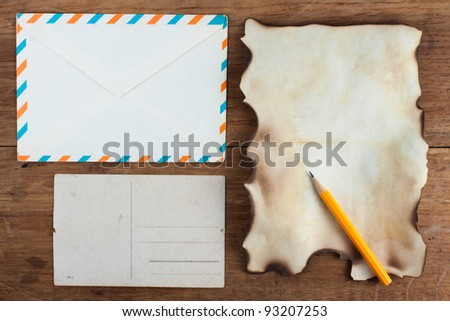 Old Burnt Paper and envelope on Wood background - stock photo