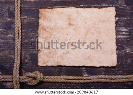 Old burnt paper on wood with rope frame background - stock photo