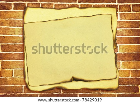 old burnt paper with burnt edges over grunge brick wall background - stock photo