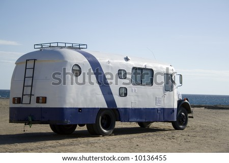 Old bus converted into a motor home parked in front of the sea, in Patagonia, Argentina. - stock photo
