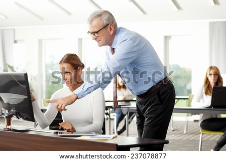 Old businessman giving advise to sales woman while working on computer at office.  - stock photo