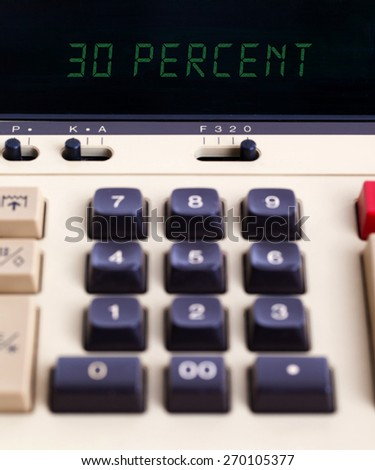 Old calculator with digital display showing a percentage - 30 percent - stock photo