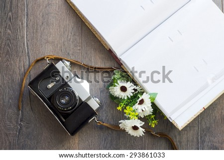 old camera and a photo album on a wooden background - stock photo