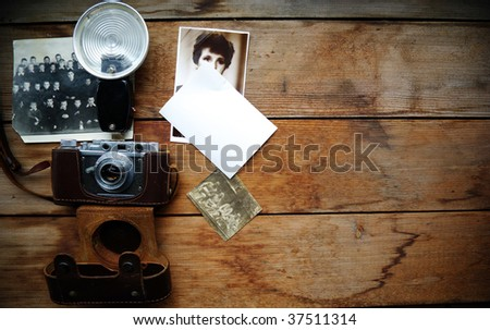 Old camera and  cards on wooden surface. Wooden background. - stock photo
