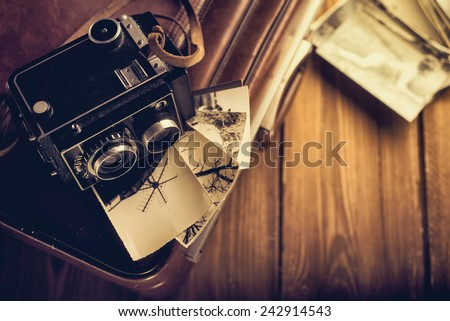 Old camera and old photos are on the case. Retouching in retro style - stock photo