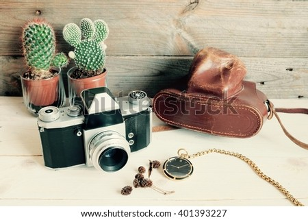 old camera and old pocket watch on wood background - stock photo