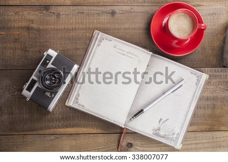 Old Camera Closeup on Brown Wood Background With Open Notepad and Coffee in Red Mug - stock photo