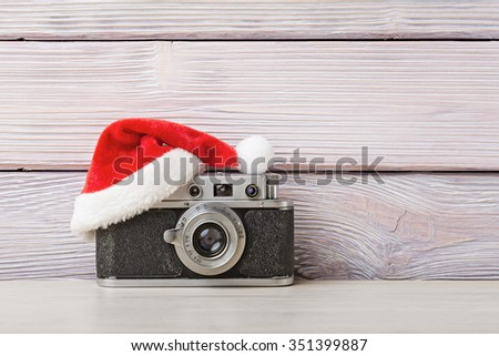 Old camera in santa hat on wooden background - stock photo