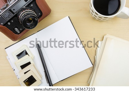 Old camera, notebook, pen and transparency slides on wooden surface - stock photo