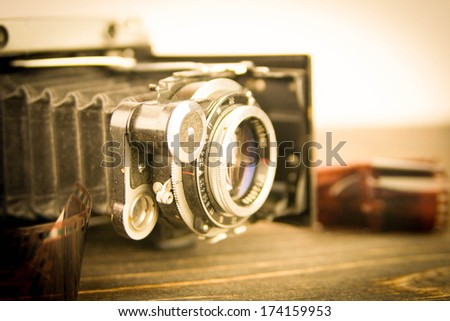 Old camera on the wooden table - stock photo