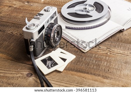 Old Camera With Film Roll and Notebook on Wood Table - stock photo