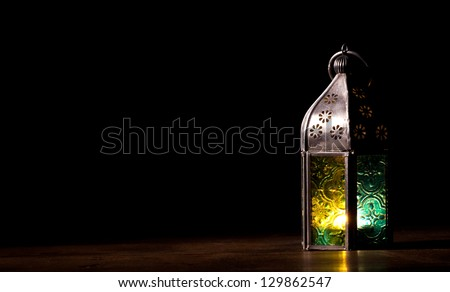 Old candle lantern on the floor in the dark - stock photo
