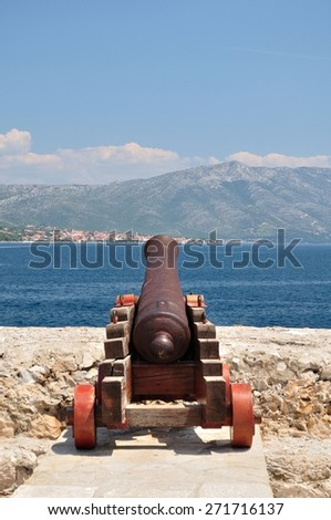 Old cannon at old fortress in medieval town Korcula in Croatia. Vertical image - stock photo