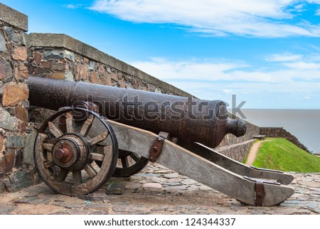 Old cannon behind the fortress wall in Colonia del Sacramento, Uruguay - stock photo
