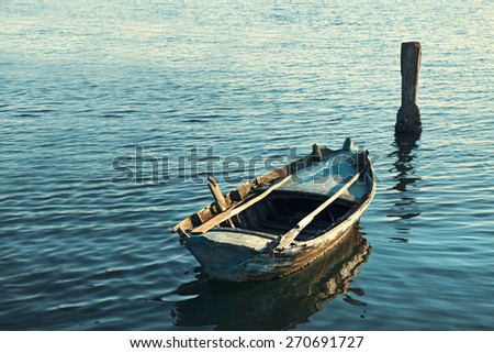 Old Canoe floating on the calm water  - stock photo