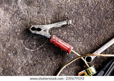 old car battery jumper on floor - stock photo