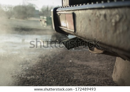 old car tail pipe with exhaust coming out, outdoor blurred shot,particular  focused on the subject - stock photo