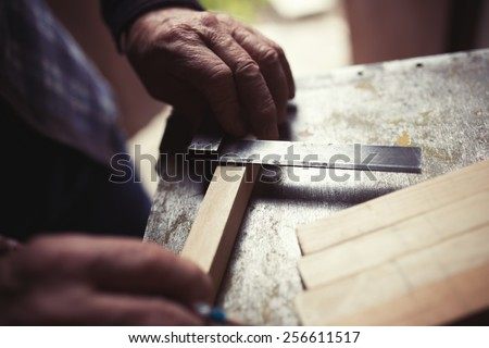 Old carpenter taking measurement of a wooden plank, retro tinted - stock photo