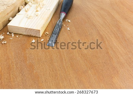 Old carpenter wood chisel tool with boards and shavings - stock photo