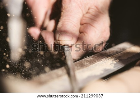 Old carpenter working with wood, retro tinted, close up photo - stock photo