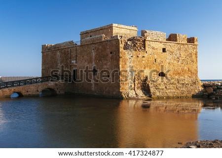 Old castle on Mediterranean sea coast. Paphos, Cyprus. Bright sunset light - stock photo