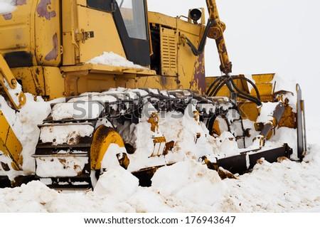Old caterpillar on a snow field - stock photo