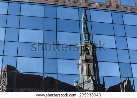Old cathedral reflected on the glass building facade - stock photo