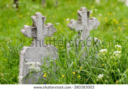 Old cemetery tombstones invaded by grass - stock photo