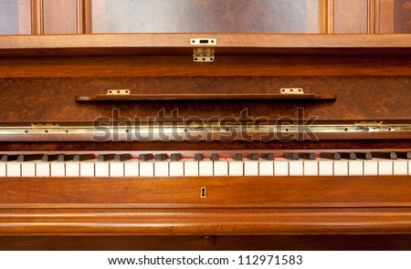 Old 19-century upright piano front cabinet with keyboard - stock photo