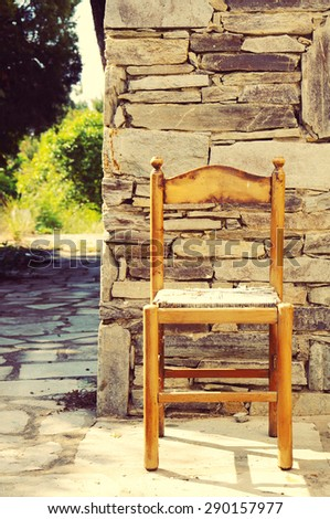 Old chair against a stone wall - stock photo