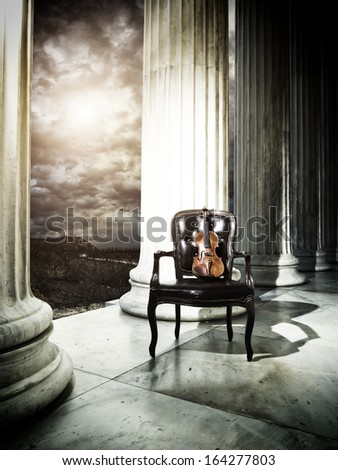 Old chair and violin at Greek temple - stock photo