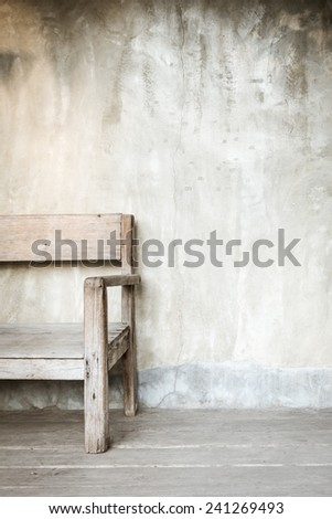 Old chair in front of concrete wall with copy space - stock photo