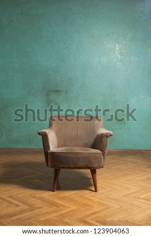 Old chair in grunge room with green wall - stock photo