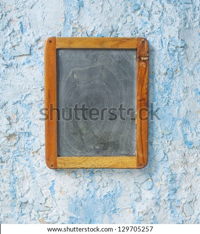 Old chalkboard on a weathered, plastered wall, free copy space - stock photo