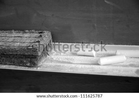 Old Chalkboard with used chalk and eraser - stock photo
