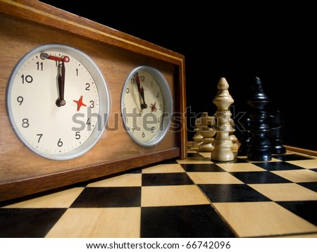 old chess clock on the chessboard with figures ,flag in position which indicates  running out of time - stock photo