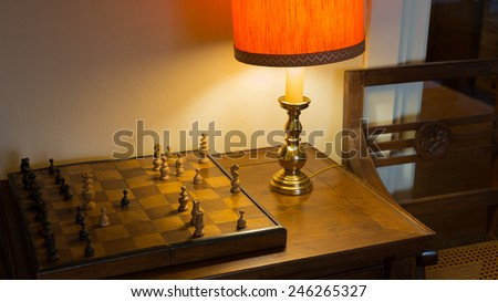 Old chessboard on writing desk and Soft Light of A desk Lamp - stock photo