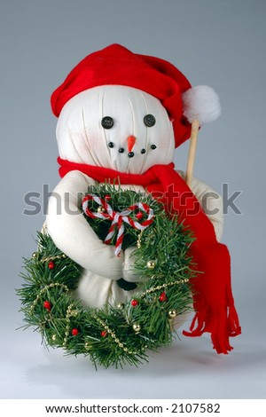 Old Christmas snowman with wreath and candy cane. - stock photo