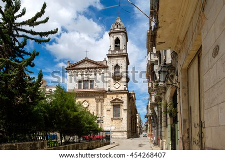 Old church and weathered buildings on a narrow street in Old Havana - stock photo