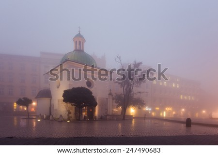 Old church on the market square in Krakow at morning fog, Poland - stock photo
