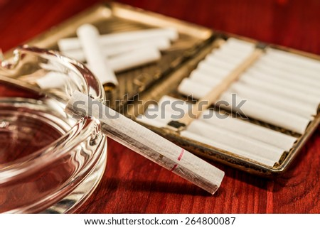 Old cigarette case with cigarettes and glass ashtray on a table in mahogany - stock photo