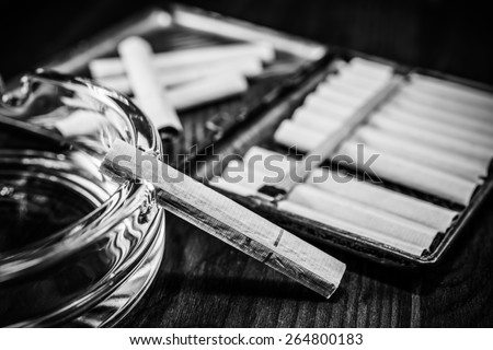 Old cigarette case with cigarettes and glass ashtray on a table in mahogany. Image vignetting and black and white tones - stock photo