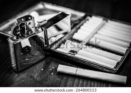 Old cigarette case with cigarettes and lighter on a table in mahogany. Focus on the cigarette, image vignetting and black and white tones - stock photo