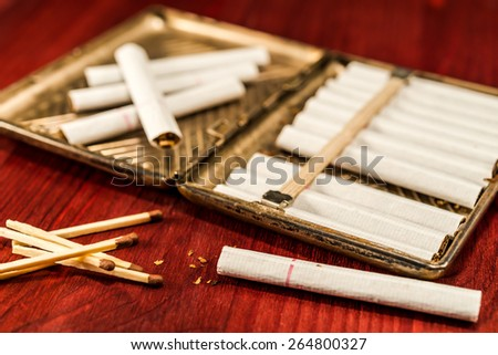 Old cigarette case with cigarettes and matches on a table in mahogany. Focus on the cigarette and matches - stock photo