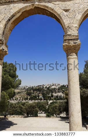 Old city of Jerusalem, Israel. Wide angle vertical view at the Mount of Olives, from between one of the arches surrounding the Dome of the Rock mosque. - stock photo