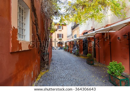 Old city street with motorbikes in Rome, Italy. On sunny autumn or spring day. - stock photo