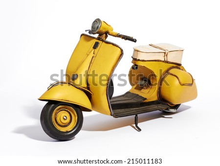 Old classic vintage yellow motor scooter with a wide foot board and saddle style seat standing upright on its stand on a white background - stock photo