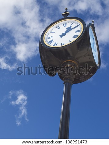 Old classical four-sided street clock over blue sky background - stock photo