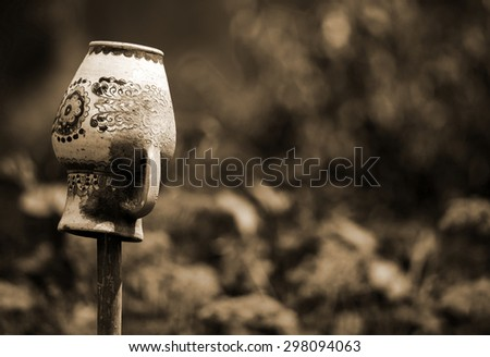 old clay jug, put on a stick in the garden - stock photo