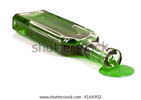 Old clear glass medicine bottle laying on it's side spilling a thick green liquid from the opening.  Isolated on white. - stock photo